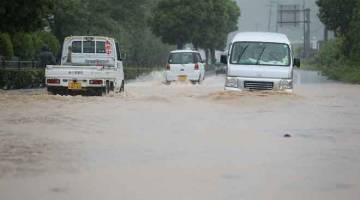 BANJIR TERUK: Kenderaan melalui jalan yang ditenggelami banjir akibat hujan lebat di Yatsushiro, wilayah Kumamoto, Jepun semalam. — Gambar AFP
