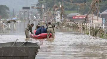 BEKERJASAMA: Anggota polis dan anggota tentera Japan Self-Defense Forces mengendali bot boleh kembung turut serta dalam usaha operasi menyelamat di rumah penjagaan berikutan hujan lebat di perkampungan Kuma, Kumamoto, semalam. — Gambar AFP