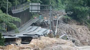 MUSNAH: Sebatang jalan terputus akibat banjir dan tanah runtuh yang dicetuskan hujan lebat dekat sungai Kuma di Ashikita, Kumamoto semalam. — Gambar AFP