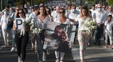 PENGHORMATAN: Veronique Monguillot (tengah) memegang gambar beliau bersama suaminya yang maut selepas diserang penumpang bas semasa perarakan di Bayonne, barat daya Perancis              pada Rabu lepas. — Gambar AFP