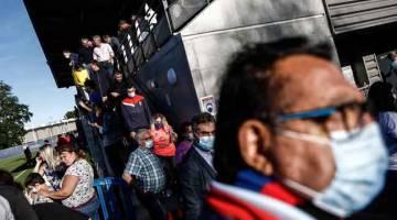 LEBIH BAIK WASPADA: Orang ramai beredar selepas menonton perlawanan persahabatan di Stadium Michel d'Ornano di bandar barat laut Caen, kelmarin. — Gambar AFP