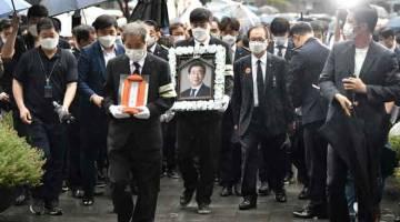 DIRATAPI: Ahli keluarga membawa potret Park semasa upacara pengebumiannya di Dewan Bandaraya Seoul di Seoul, semalam. — Gambar AFP