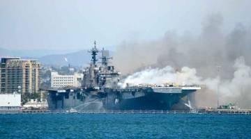 TERBAKAR: Gambar serahan Tentera Laut AS menunjukkan bot jabatan polis dan bomba pelabuhan cuba memadam api di atas USS Bonhomme Richard di Pangkalan Tentera Laut San Diego, kelmarin. — Gambar AFP
