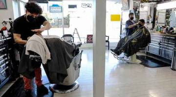 PATUHI SOP: Tukang gunting rambut dan pelanggan mematuhi SOP dengan memakai pelitup muka di sebuah salun rambut                   di Los Angeles, California kelmarin sejurus sebelum gabenor negeri itu mengarahkan penutupan semula premis perniagaan              dan rumah ibadat untuk mengekang penyebaran COVID-19. — Gambar AFP