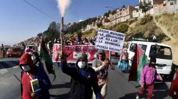 PROTES: Penunjuk perasaan berarak dari El Alto ke jalan utama di La Paz untuk memprotes dasar kesihatan, pendidikan dan buruh di bawah kerajaan Presiden Jeanine Anez kelmarin, mengingkari  sekatan kuarantin yang dilaksanakan untuk membendung penularan COVID-19. — Gambar AFP