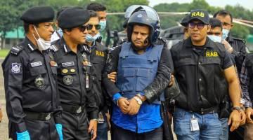 DIBERKAS: Anggota Batalion Tindakan Pantas mengiringi Mohammad Shahed (tengah) yang ditangkap selepas hospital miliknya dituduh mengagihkan sijil palsu negatif COVID-19 kepada pesakit di Dhaka, Bangladesh kelmarin. — Gambar AFP