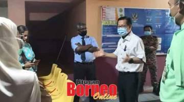 TINJAU: Lee bercakap kepada petugas Pejabat Kesihtan Miri semasa mengadakan tinjauan ke pusat sehenti bagi pemeriksaan COVID-19 di Stadium Tertutup Miri semalam.