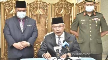 PENJELASAN: Abinan (tengah) ketika menyampaikan kenyataan rasmi TYT Sabah di Istana Negeri, Kota Kinabalu.