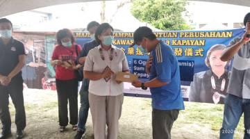 SUMBANGAN: Jannie (kiri) menyampaikan sumbangan kewangan kepada peniaga kecil di Kapayan semalam.