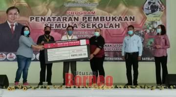 SUMBANGAN: Wakil Yayasan Sarawak Baithy Tini (kiri) menyampaikan replika cek bantuan pakaian sekolah kepada Timbalan PPD Sebauh Mohamad Nor pada majlis tersebut.