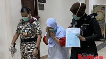 Eva semasa diiringi pegawai penjara di lobi Mahkamah Kuching, hari ini.
