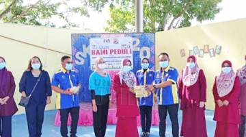 SUMBANGAN: Iswadiman (lima, kanan) menyampaikan sumbangan pelitup separuh muka dan cecair pembasmi kuman kepada Guru Besar SK Merpati pada Program Kami Peduli di dewan terbuka sekolah itu.