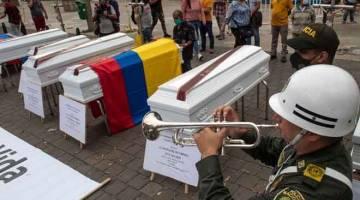 PROTES KEGANASAN: Anggota polis meniup trompet di sebelah beberapa keranda yang                     diperagakan sebagai sebahagian daripada protes terhadap keganasan di Colombia di mana beberapa pembunuhan berlaku sejak beberapa hari lalu di Medellin pada Isnin lepas. — Gambar AFP