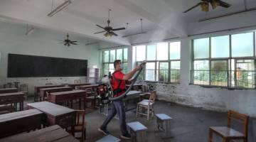 NYAHKUMAN: Seorang sukarelawan menyembur bahan nyahkuman di sebuah bilik darjah sebuah sekolah sebelum bermulanya semester baharu di Handan di wilayah Hebei, China. — Gambar AFP