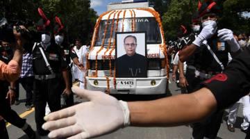 PENGHORMATAN TERAKHIR: Anggota tentera mengiringi ambulans yang membawa mayat             bekas presiden India Pranab Mukherjee di luar kediamannya sebelum upacara pengebumiannya di New Delhi kelmarin. — Gambar AFP