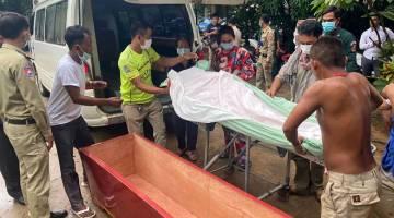 TIADA LAGI: Saudara mara mengangkat mayat Kaing Guek Eav (sisipan) dari ambulans untuk upacara pengebumian di sebuah pagoda di Phnom Penh semalam. — Gambar AFP