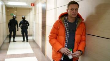KENA RACUN: Gambar fail diambil pada 26 Disember, 2019 menunjukkan Alexei Navalny               berdiri berhampiran dengan ejen penguat kuasa undang-undang di ruang depan sebuah pusat perniagaan yang menempatkan pejabatnya, Yayasan Anti-Rasuah (FBK), di Moscow. — Gambar AFP