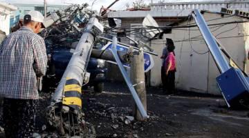 ANGKARA MAYSAK: Penduduk memandang tiang elektrik yang tumbang selepas Taufan Maysak melanda di bandar pelabuhan tenggara Ulsan semalam. — Gambar AFP