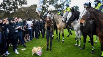 TIDAK PUAS HATI: Pembantah berhadapan dengan polis di Tugu Peringatan di Melbourne kelmarin, ketika rali protes anti sekatan pergerakan yang dikuatkuaskan oleh pihak kerajaan bagi mengekang penularan COVID-19. — Gambar AFP