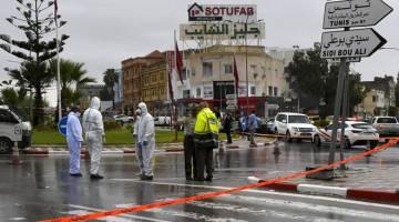 KECOH: Anggota polis forensik memeriksa tempat kejadian yang menyaksikan seorang pegawai maut dan seorang lagi cedera di Sousse, selatan Tunis kelmarin. — Gambar AFP