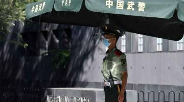 KRISIS TERBAHARU: Seorang anggota polis separa tentera berkawal di luar kedutaan Australia di Beijing, semalam. — Gambar AFP