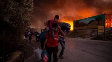 KEBAKARAN BESAR: Pencari suaka bersama kanak-kanak dilihat melarikan diri dari kebakaran besar yang meletus di kem pendatang Moria di pulau Lesbos, Greece kelmarin. — Gambar AFP