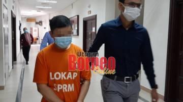 Suspek diiringi pegawai SPRM semasa berada di Mahkamah Kuching.