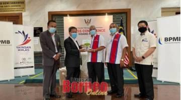 Dr Sim (dua kiri) menerima cenderahati daripada Rosli pada majlis itu sambil disaksikan oleh (dari kiri) Daud, Rosli, Kamaruddin dan Salihin