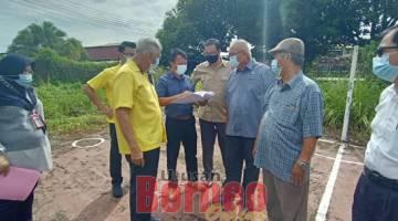 NAIK TARAF: Ting (dua kiri) bersama Yii (dua kanan) mendengar penerangan daripada jurutera MBM tentang projek menaik taraf gelanggang sepak takraw Kampung Piasau Utara semalam.