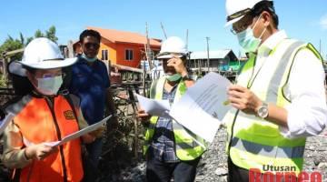 Dr Abdul Rahman (kanan) mendengar penerangan ringkas dari pegawai JKR berhubung projek di Kampung Buntal.