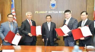METERAI: Shafie (tengah) menyaksikan pertukaran dokumen di antara Jamalul (dua kiri) dan wakil TBSB Jerrand Lim Jen Jiang (dua kanan) bersama tetamu kehormat lain pada majlis berkenaan.