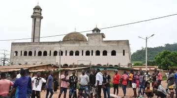 KACAU: Komuniti Muslim tempatan berhimpun di hadapan sebuah masjid di Bongouanou, kelmarin selepas dua hari keganasan antara komuniti menjelang pilihan raya presiden pada 31 Oktober ini. — Gambar AFP