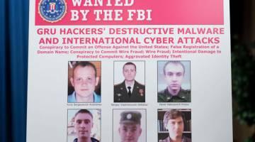 DIDAKWA: Poster menunjukkan gambar enam pegawai perisik tentera Rusia dipamerkan sebelum sidang media di Jabatan Kehakiman di Washington, kelmarin. — Gambar AFP