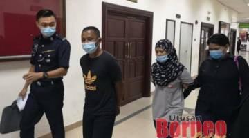 Suami isteri tersebut diiring polis semasa berada di Kompleks Mahkamah Kuching.