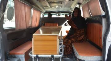 TRAGIK: Seorang wanita duduk di sebelah keranda ahli keluarganya yang terbunuh dalam insiden rempuhan di Jalalabad, semalam. — Gambar AFP