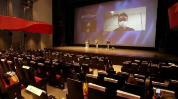 PENJARAKAN SOSIAL: Gambar ihsan yang diambil dan dikeluarkan oleh BIFF menunjukkan pengarah filem Korea Selatan Yeon Sang-ho dipaparkan di skrin semasa perbahasan umum mengenai filem zombi 'Peninsula' semasa BIFF 2020 di Busan Cinema Center di Busan. — Gambar BIFF / AFP