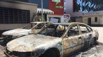 ROSAK: Dua kereta rosak selepas dibakar penunjuk perasaan yang menyerang pusat beli-belah kelas pertengahan di Lekki Phase 1, Lagos kelmarin. — Gambar AFP