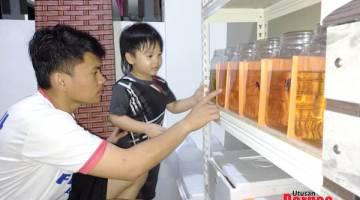 MEMUKAU: Asmawie bersama anak lelakinya melihat kecantikan ikan laga miliknya.