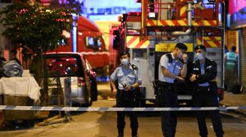 TENANG: Pegawai polis berkawal berhampiran trak bomba di lokasi kebakaran di Hong Kong, awal semalam. — Gambar AFP