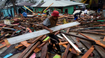 RANAP: Seorang lelaki mengangkat papan untuk membaiki rumahnya yang ranap selepas                   Taufan Iota melanda Bilwi di Nicaragua kelmarin. — Gambar AFP