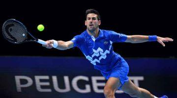 BERAKSI TANGKAS: Aksi Djokovic semasa menentang Zverev dalam Kejohanan Final Jelajah ATP di O2 Arena di London. — Gambar AFP