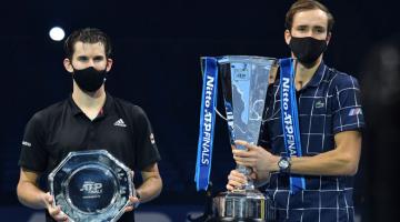 UNTUK KENANGAN: Medvedev (kanan) dan Thiem memakai pelitup muka bergambar dengan trofi selepas perlawanan di O2 Arena di London kelmarin. — Gambar AFP
