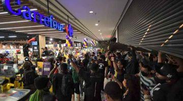 SUARA MARAH: Penunjuk perasaan menceroboh pasar raya Carrefour di Sao Paulo, Brazil pada Jumaat lepas untuk membantah tindakan pengawal keselamatan memukul sehingga mati seorang lelaki kulit hitam. — Gambar AFP