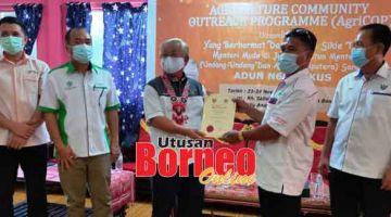 TAHNIAH: Sikie (tiga kiri) menyampaikan sijil kursus AgriCOP kepada Tuai Rumah Salleh di Nanga Bena, Ulu Anap Tatau kelmarin.