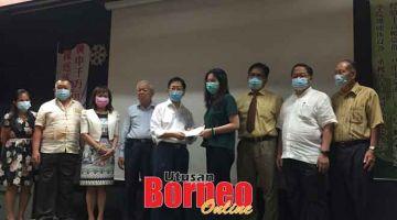 TERUSKAN USAHA: Lau (lima kiri) menyampaikan biasiswa kepada salah seorang penerima di SM Wong Nai Siong.