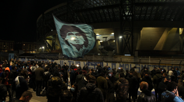 LEGASI DITERUSKAN: Orang ramai berkumpul di hadapan Stadium San Paolo tanda berkabung di atas pemergian legenda Maradona akibat serangan jantung. — Gambar AFP