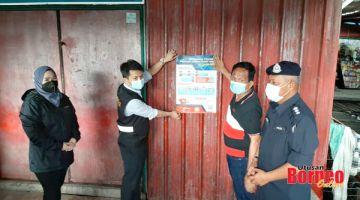 KESEDARAN: Mohd Azhar (kanan) bersama Timbalan Presiden MPS, Farizah Giau (kiri) melihat sendiri penampal poster 'Bersama Cegah Penyakit Covid - 19' oleh kakitangan kesihatan sempena operasi bersepadu di Kg Bahagia, Batu Sapi.