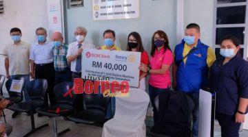 Dr Sim (tengah) menyaksikan penyerahan cek sumbangan daripada OCBC Bank kepada Pusat Dialisis NFK Kota Samarahan di Kuching hari ini. Gambar Muhammad Rais Sanusi.