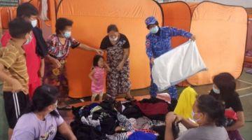Pasukan APM Bintulu mengagihkan bantuan pakaian kepada mangsa banjir.