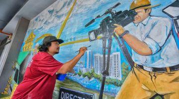 Pelukis mural, Kassmadi Morshidi, 42, menyiapkan lukisan mural di bangunan Radio Televisyen Malaysia (RTM) Sarawak di Kuching iaitu projek terbaharu mereka. - Gambar BERNAMA.